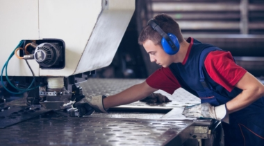 Photo of a young male sheet metalworker using a large machine