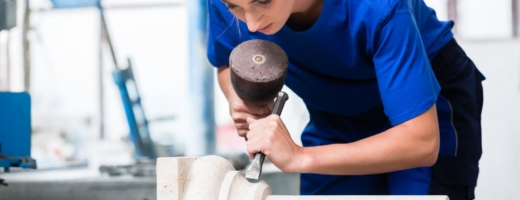 Photo of a young female stonemason with a chisel on part of a pillar