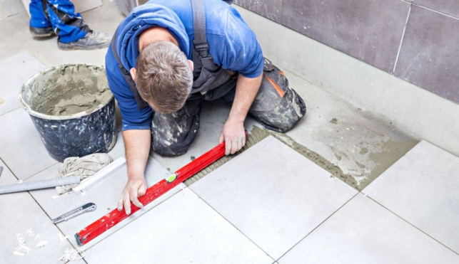 Photo of a tiler using a spirit level to lay floor tiles