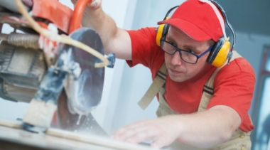 Photo of a young tiler cutting a tile with ear defenders on