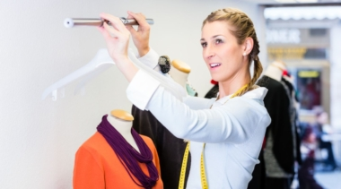 Photo of a Visual Merchandiser adjusting a clothes rail with hangers