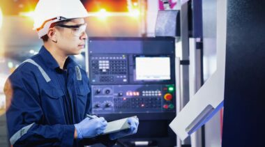 Photo of industrial control technician examining machine