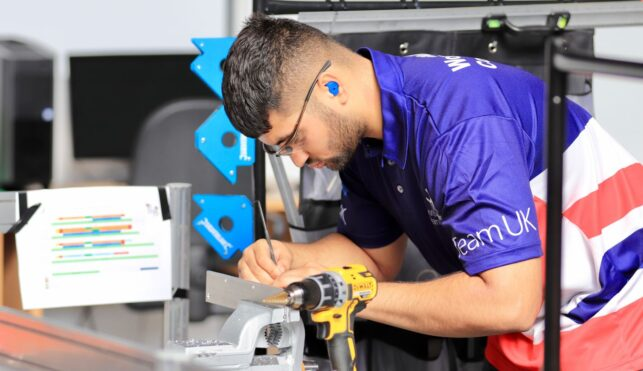 Photo of Isaac competing internationally in the Manufacturing Team Challenge