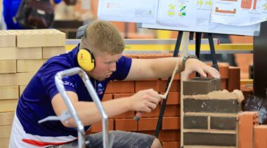 Photo of Lewis competing internationally in the bricklaying competition