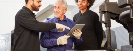 Photo of mechatronics engineers reviewing iPad chart next to machinery