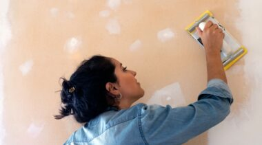 Photo of plasterer smoothing wall