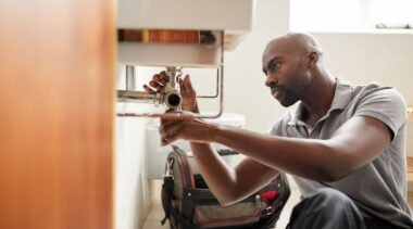 Photo of plumber examining under the sink pipework