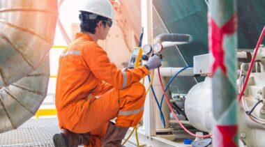 Photo of refrigeration engineer examining pipework
