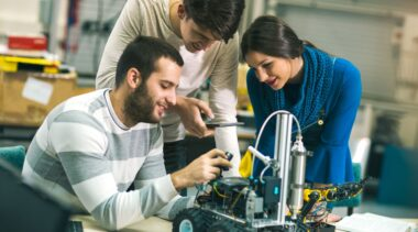 Photo of robotics engineers examining robot parts