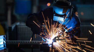 Photo of sheet metalworker in protective gear using power tool