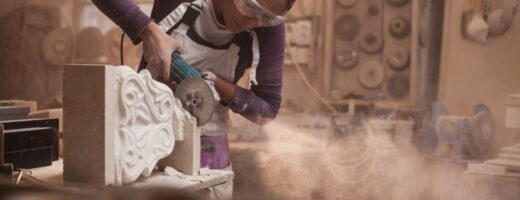 Photo of stonemason using power tool to work on decorative stone item