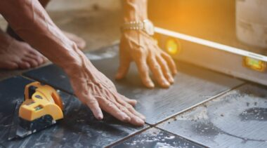 Photo of tiler placing tile on floor with spirit level