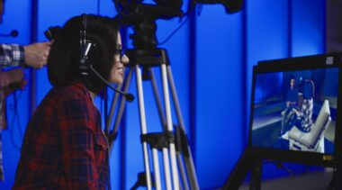 Photo of TV producer overseeing filming behind camera