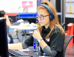 Girl wearing headphones and working at computer