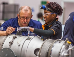 Training manager helping female competitor in aircraft maintenance