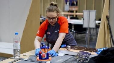 Female tiling competitor cutting tiles