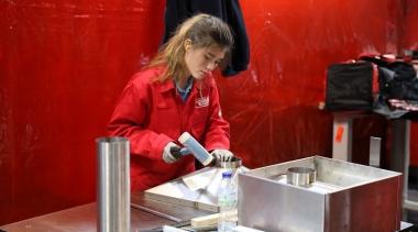 Female competitor hammering metal