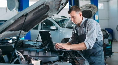 Photo of car mechanic using a computer laptop to diagnosing and checking up on car engines parts for fixing and repair